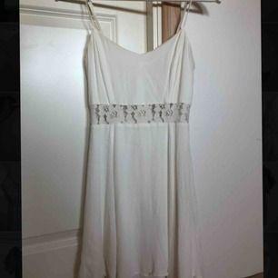Vit klänning med spetsdetaljer, använd vid två tillfällen, säljer pga för liten
