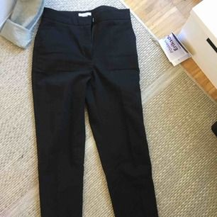 Slacks/ svarta kostymbyxor  Lite slits vid vaden.  Fickor där fram