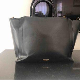Svart läder (inte äkta) väska. Köpte i Nice, Frankrike. Väskan har två yttre fack (en på varje sida) och tre fack i väskans mitten fack. Möts gärna upp vid köp av väskan men kan också skicka via post (köparen står för frakten)