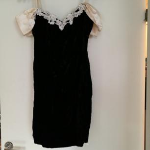 Svart cocktail klänning som jag säljer på grund av att den är för lite för mig. Har en fin vit rosett på baksidan samt ett tyg som liknar sammet.