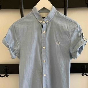 Slim fit short-sleeved dress shirt with cool details on the sides. Brand: Fred Perry Size: XS Fit: Slim Fit Colour: Light Blue  Used but still in good shape. really good fit.