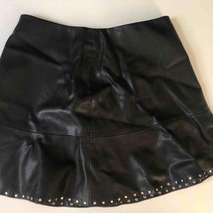 Fake-läder kjol med nitar längs kanten. Knappt använd då den var för stor på mig. Fraktpris ingår ej. Pris kan diskuteras.