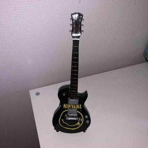 Handgjord unik gitarr dekoration med Nirvana motiv! I fint skick!! Kommer med ställ. Frakt ingår i priset
