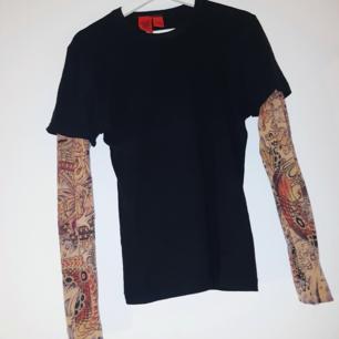 Skitball t-shirt med inbyggd långärmad tröja som ska likna  sleeve tattoos typ. Märket är