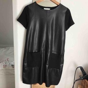 Svart T-shirt klänning med fejk läder på framsidan. Stickad baktill. Säljes då den inte kommer till användning. Nypris 400, säljer nu för 150 kr.  Köparen står för frakt.