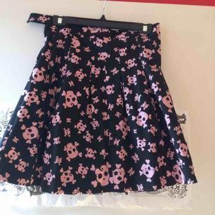 Dags att skiljas från en älskad ägodel. Svarta klockad kjol med rosa döskallar (de ser vita ut men är rosa). Stl 36 men funkar på 38 också. Stängs med dragkedja o hyska i sidan. Använd men i mkt fint skick. Frakt tillkommer med 55 kr.