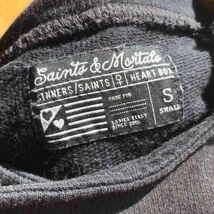 """En svart hoodie """"utan ärmar""""/kortärmad. Tre fickor. Skön, bra till sommaren."""