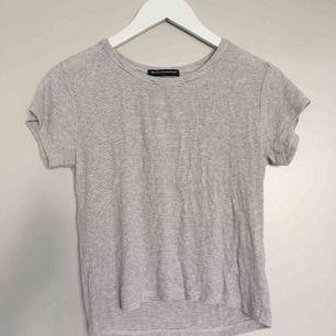 Grå vit randig T-Shirt med mkt stretchigt material som passar alla storlekar från S-XL. Aldrig använd och är i mkt bra skick