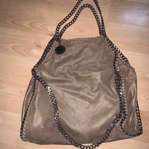 Stella Mcartney väska falabella modell. Äkta. Kommer med dustbag. Använd men i fint skick, hel & fin men lite sliten & mörkare än när den köptes. Beige. På bilderna här ser det ut som att det är röda fläckar. Så är det inte IRL. Konstigt!!