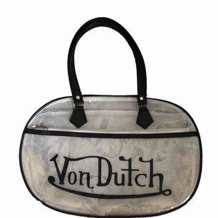 Säljer denna Sjukt snygga men även unika väska från märket Von Dutch.   Väskan är genomskinligt med nät inuti och pryds av en stor printad logga