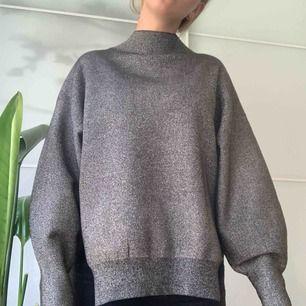 Grå-glittrig tröja från H&M. Slits på sidan. Mycket skön! Inga skador, mer eller mindre i nyskick. Eventuell frakt tillkommer, möts annars upp i centrala Stockholm