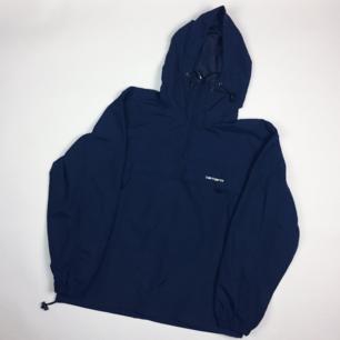 Carhartt mörkblå pullover vindjacka i stl L. Unisex modell som funkar på alla. Dold bröstficka och två fickor i sidorna. Frakt 63 kr.