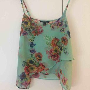 Transparent turkost/mintgrönt linne med blommor i härliga färger. Från Forever 21/XXI i strl S med justerbara axelband.  Frakt: 39kr eller spårbart 63kr