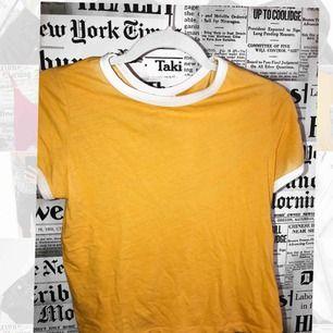 En fin gul t-shirt, med vita detaljer runt halsen samt där vid armarna