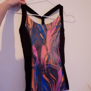 Träningslinne med inbyggt stöd för brösten! Fina färger och mönster med en snygg skärning i ryggen! Helt oanvänd😍