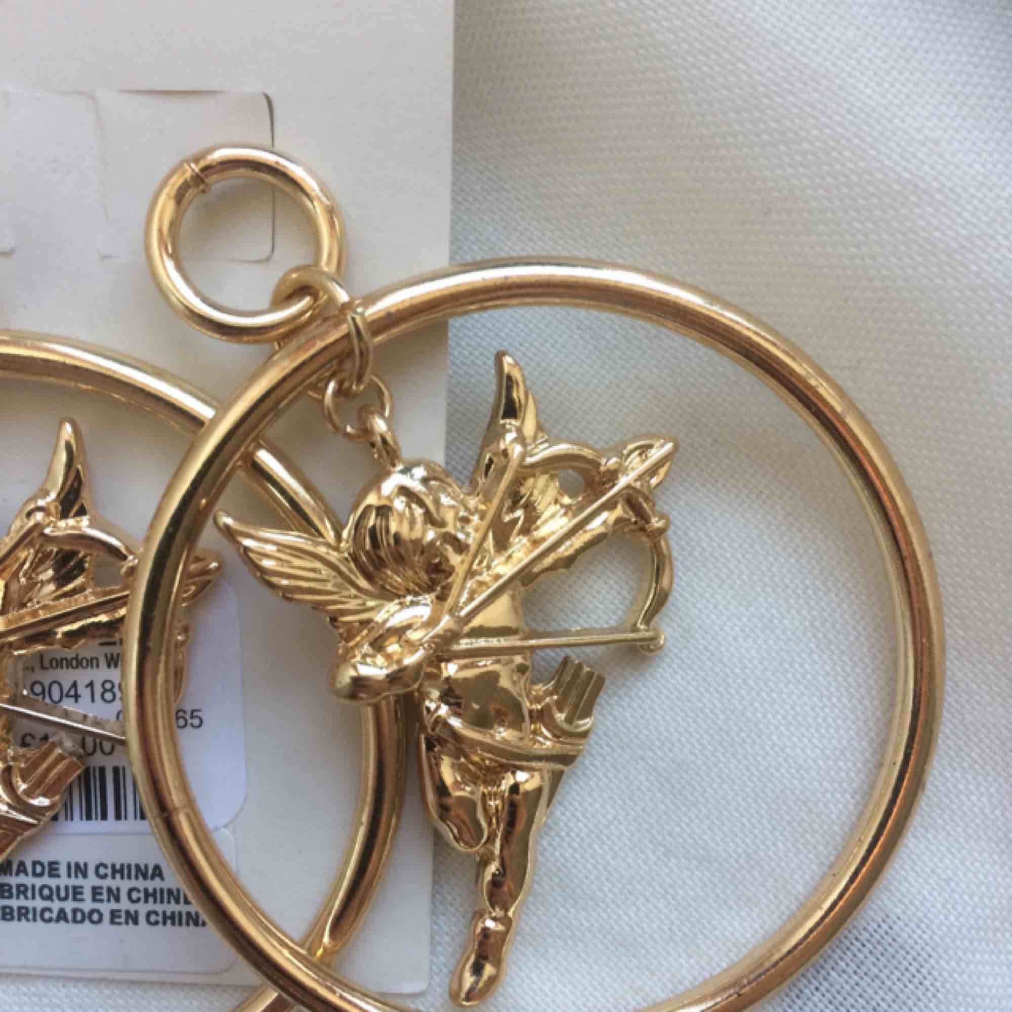 Säljer de här helt nya örhängena från Urban Outfitters. Så fin och unik design med små änglar!   Ursprungspris 200kr.. Accessoarer.