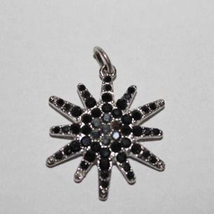 Berlock i form av svart och silver stjärna. Ej äkta silver!