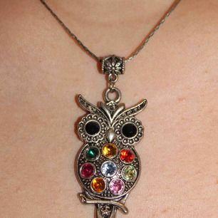 Halsband med berlock i form av uggla. Ganska styv kedja. Ej i äkta silver.
