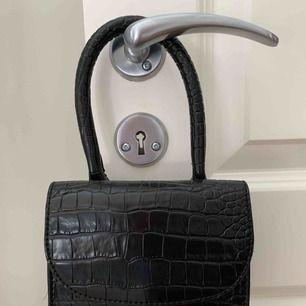Helt ny accessoar väska. Köpt från Nelly. Aldrig använd. Svart med ormskinn. Köparen står för ev frakt.
