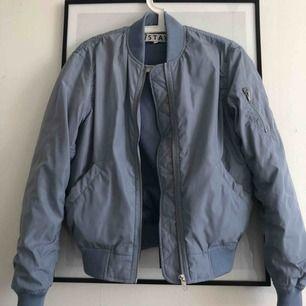 Blå bomberjacka i storlek S från märket /Stay! Jag är vanligtvis storlek xs så den sitter ganska oversized på mig. Frakt tillkommer