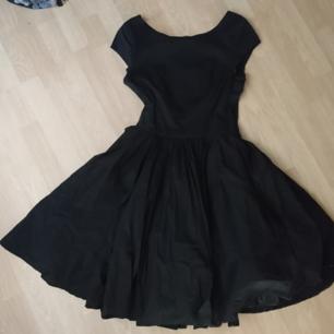 Svart, 50-tals klänning med underkjol i tyll. Dragkedja bak.  Använd en gång