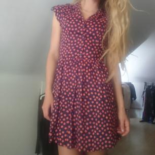 Supersöt klänning med mörkblå bakgrund och stora orangea prickar. Knappar fram