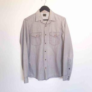 Snygg ljusgrå jeansskjorta med kopparfärgade knappar och ett par snygga knappar som detaljer. Bra skick.  Stl M  Har Swish. Kan skickas. Djurfritt & rökfritt hem.