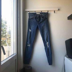 Blåa jeans med hål från gina