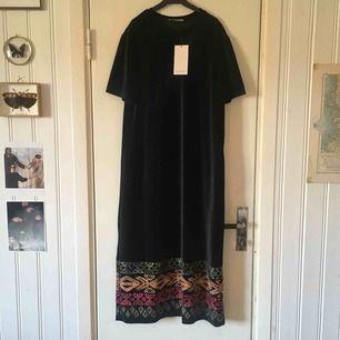 Långklänning fr Zara i svart sammetstyg, med en broderad kant längst ner. I nyskick, aldrig använd.