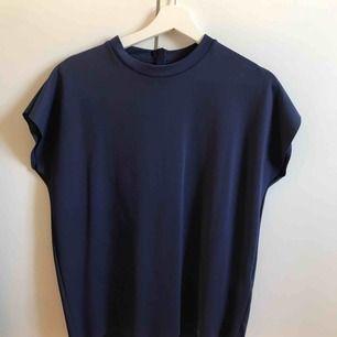 Festligare t-shirt i marinblått, superbra kvalité som känns lite lyxigare. Endast använd en gång, ser helt ny ut. Frakt ingår