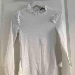 Söt vit långärmad tröja med volanger, använd 1 gång.150 kr ink frakt