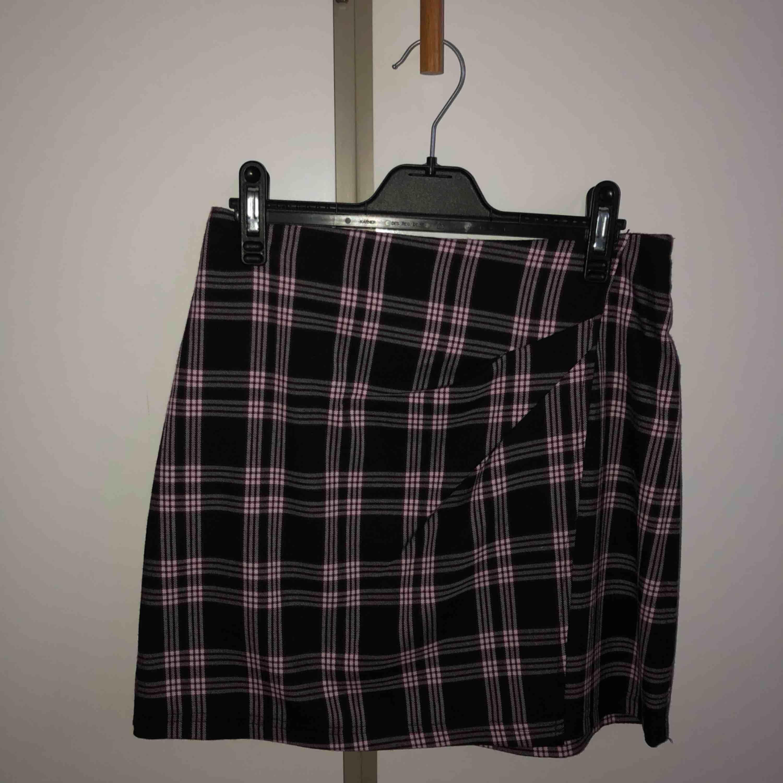 En jättefin rutig kjol köpt från Nelly Trend. På bilderna ser den svartvit ut men den är babyrosa och svart.  Säljer kjolen pågrund av att den är numera för liten för mig. Knapp använd, bra skick.   Köparen står för frakten.. Kjolar.