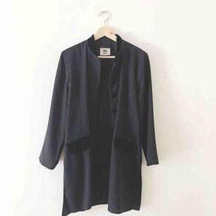 Svart lätt kavaj med kinakrage och liten axelpuff. Polyester med detaljer i svart sammet. Hel och ren.