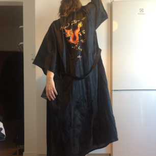 Svart kimono med diskret svart mönster och broderad drake på ryggen. Bälte i midjan och två fickor fram. Cool att ha som jacka/kofta på sommaren när det är varmt! Frakt 55 kr.