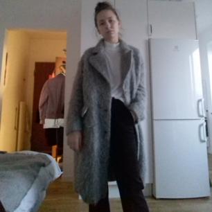 Grå ullig kappa från H&M Trend i stl 34. Borstad ull och gjord i ull, mohair & alpaca. Oversize, knäpps med 3 knappar, finns en 4e knapp högt upp om man vill ha den knäppt hela vägen upp. Köpt för tusen kronor för två år sen. Frakt 63 kr.