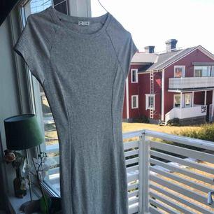 En lite längre grå klänning som går ungefär till strax nedanför knäna. Super fin och perfekt för sommarn. Är i storlek XS men fungerar bra på S. Använd en gång. Frakten går på 60kr, för bättre bilder skriv privat