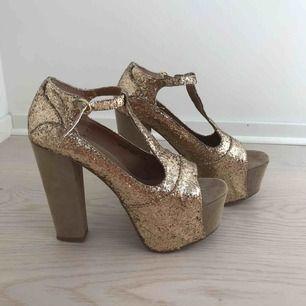 Guldglittriga högklackade skor i nyskick. De är använda endast två gånger. 13 cm klackhöjd. Köparen står för fraktkostnad enligt postens portotabell.