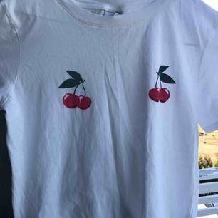 Super fin vit t shirt med körsbär på bröstet. Perfekt till sommarn, använd ett fåtal gånger. Frakten går på 50kr.