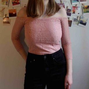 Ljusrosa, off-shoulder tröja med mönster i spets, ärmarna är endast i spets. Tight fit, speciellt ärmarna. Aldrig använd då den var för tight för mig. Brukar i vanliga fall ha S så skulle säga att denna passar bättre som XS.
