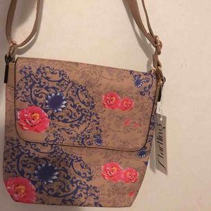 Säljer en blommig väska som inte är använd prislappen ligger fortfarande kvar. Kan skicka väskan men då står köparen för frakten