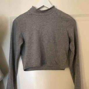 En croppad tröja från bikbok tror jag, den har halv polo. Skönt stretchigt material frakt tillkommer.