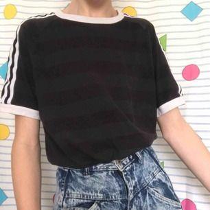 ♻️ Vintage ♻️ adidas t-shirt i en grå och svart färg med vita ränder på armarna 🖤 Tröjan är i fint skick 😍 Frakten ligger på 36kr 📨 Hör av dig om du har några frågor ❓