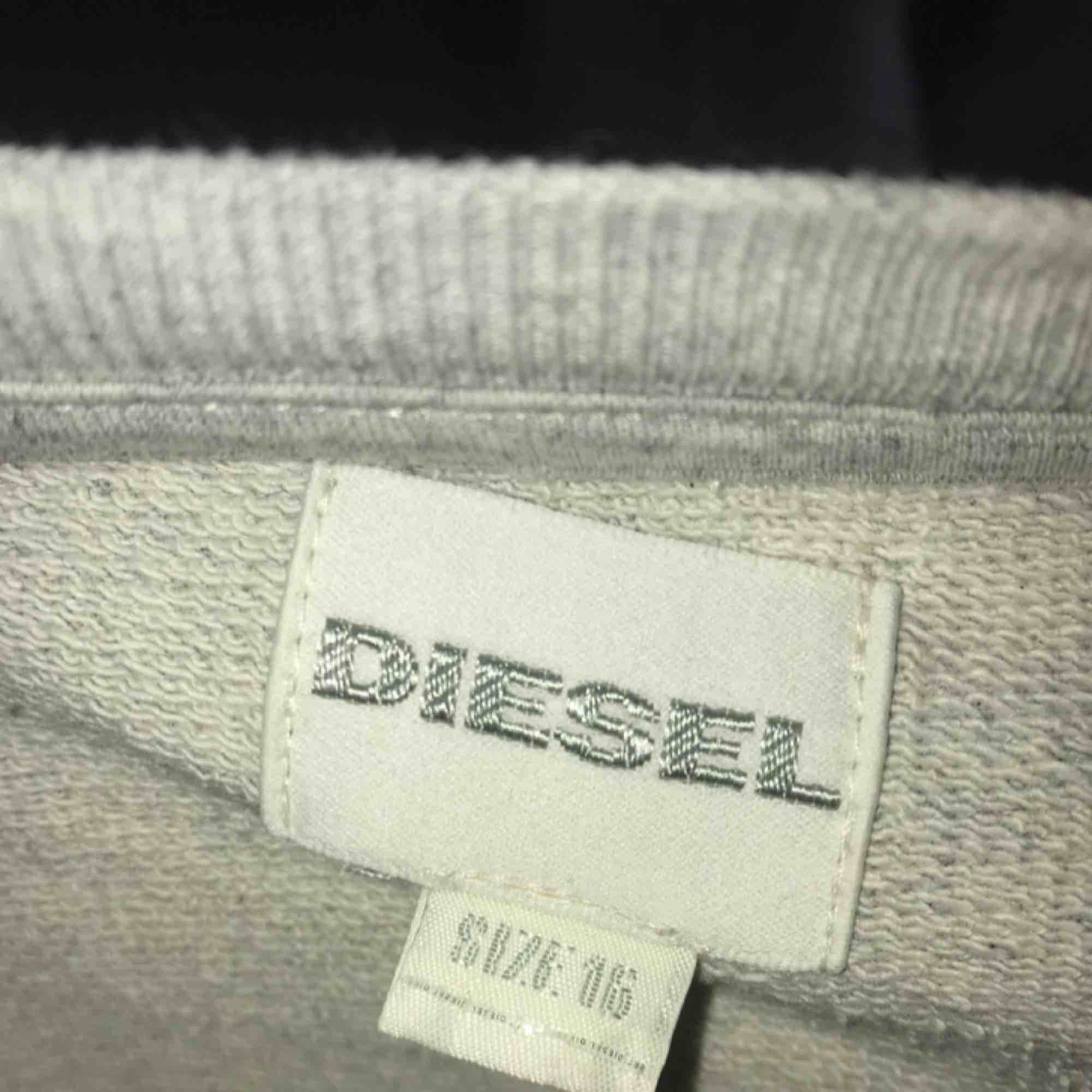 En väldigt snygg avklippt sweatshirt från diesel. Säljer pågrund av för lite användning :/ Den är grå med ett svart vit märke i mitten och sitter som en lite längre magtröja. Nypris: 200kr men säljer för 60kr+frakt. Toppar.