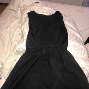 En ganska kort svart klänning med detaljer vid magen