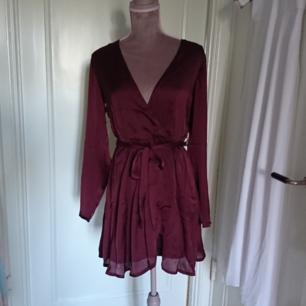 Vinröd omlott satin klänning från nelly. Frakt 26kr betalning via swish