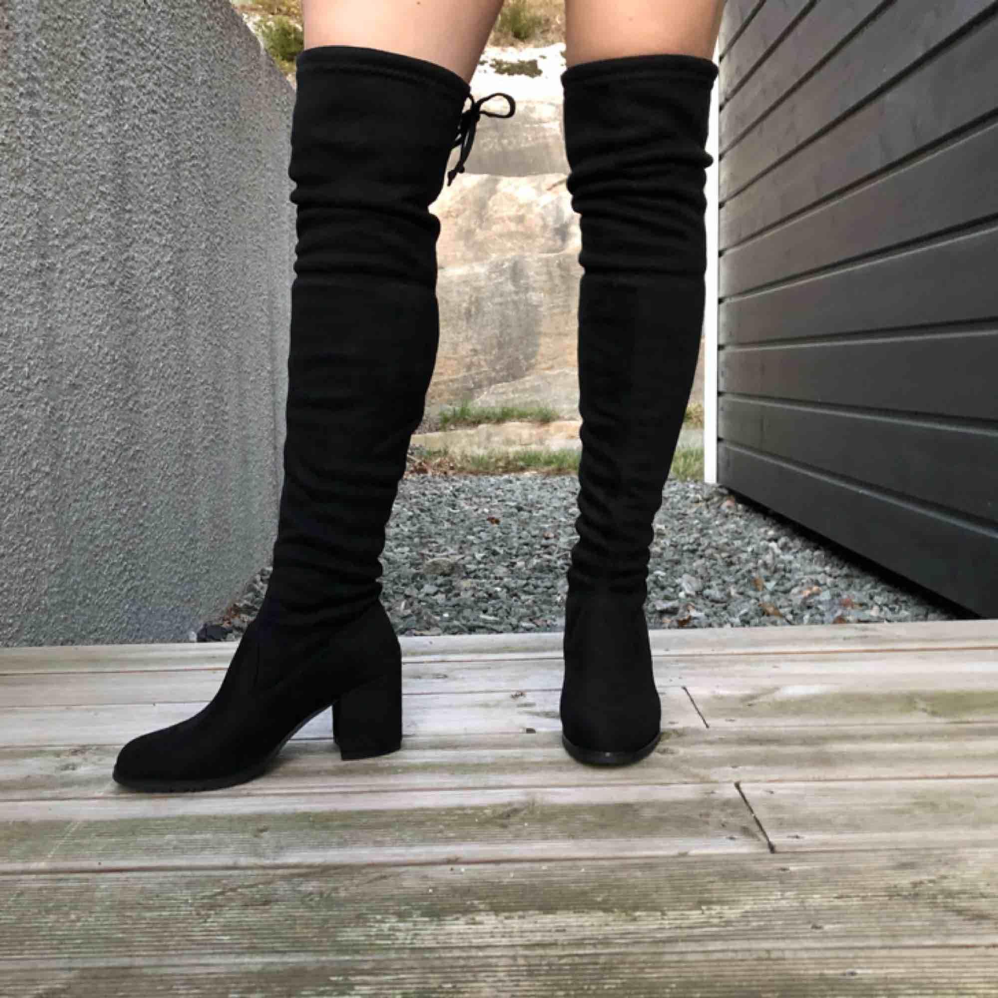Lårhöga boots i sammet med praktisk knytning baktill. Aldrig använda! Säljer för mina fötter är lite för stora. Mina mått är: Över knäna 39 cm. Vad 34 cm. Fotlängd 24 cm. Fotbredd 9 cm. Köparen står för frakt kan annars mötas i GBG.. Skor.
