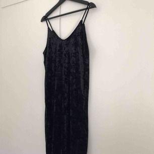 En jättesnygg svart sammetsklänning. Lite lösare modell. Superfin med ett skärp runt midjan. Frakt tillkommer.