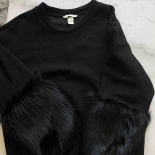 Sweatshirt med fejkpäls detaljer på ärmarna. Jättefin skick! Frakt tillkommer på 63kr.