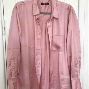 Helt NY blus i fint glansigt material!  Aldrig använd. Perfekt till sommaren, jättefint rosa färg.