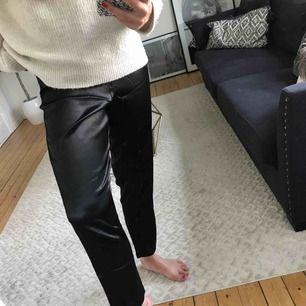 NYA kostymbyxor i svart glansigt material.  Byxorna har resår i midjan & dragkedja vilket gör att de anpassar sig efter din kroppstyp.  Jättesnygga både till festligare tillfällen & vardags.